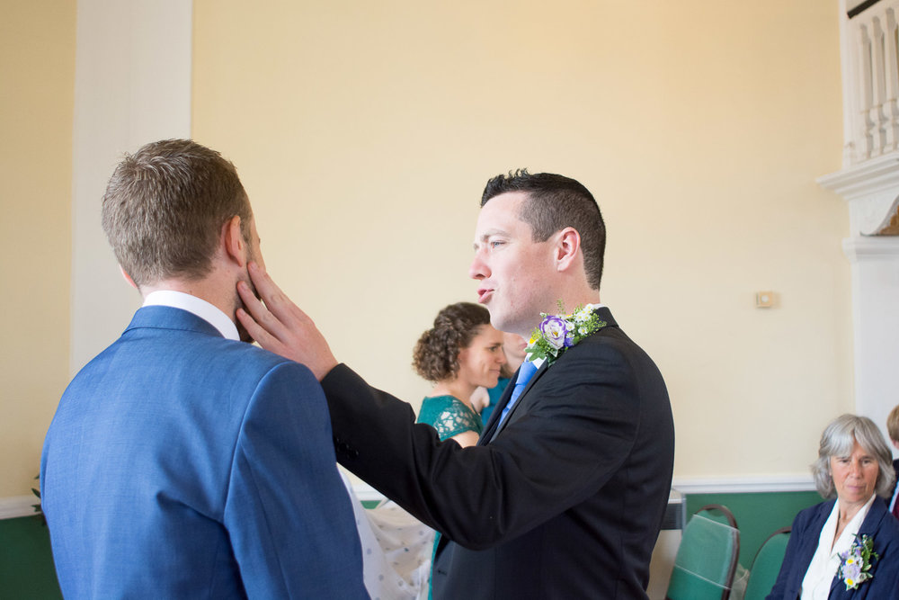 best man gives the groom a little slap on the face for encouragement at lutterworth town hall