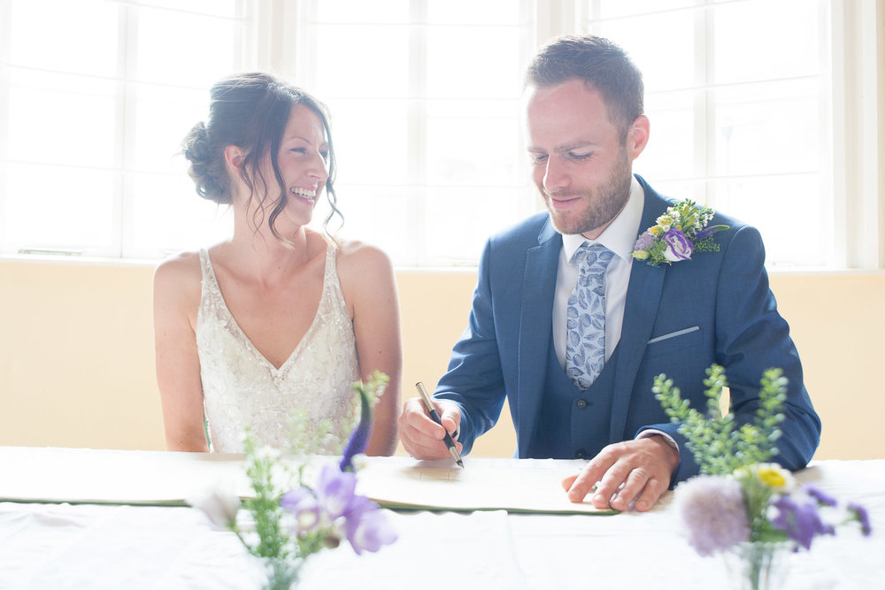 bride and groom pretend to sign the register at lutterworth town hall