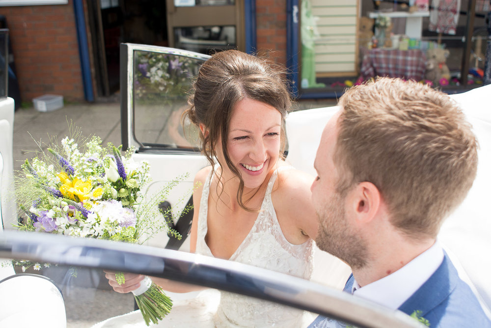 bride and groom sat in convertible vw beetle