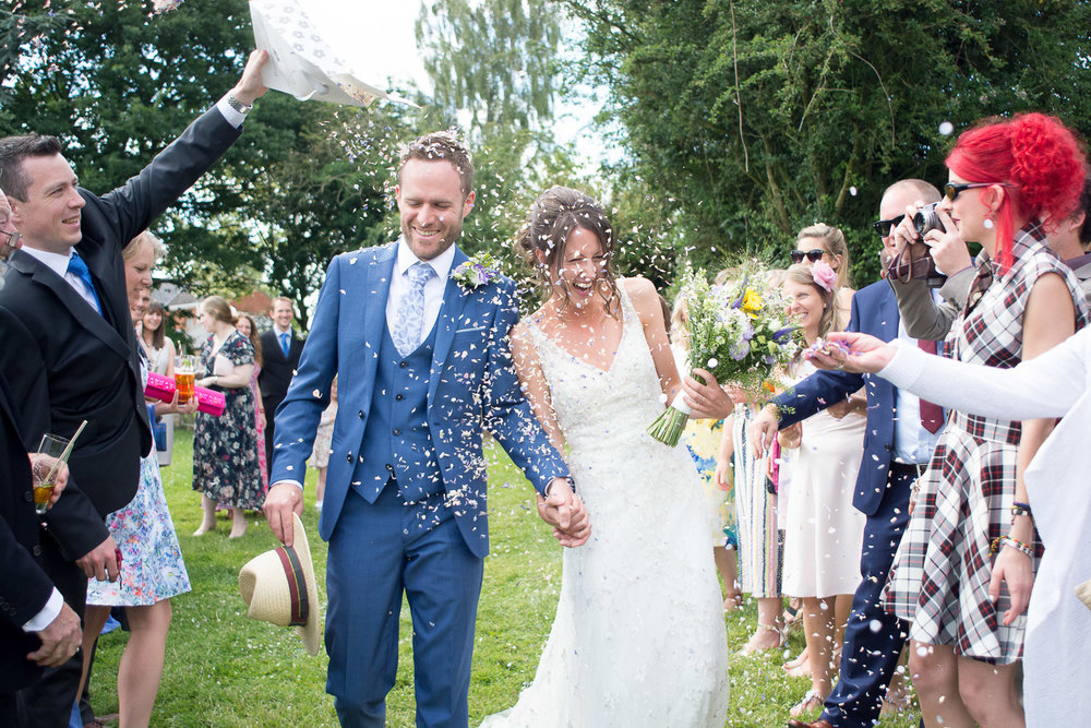 bride and groom walk through confetti at wedding yurts wedding in leicestershire
