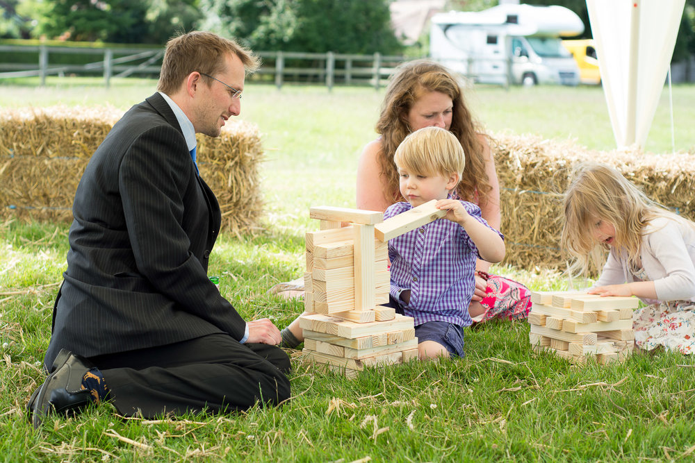 boy and his dad play jenga at wedding yurts wedding in leicestershire