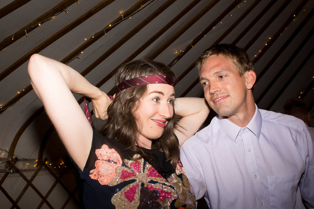 girl ties a tie around her head at wedding yurts wedding in leicestershire