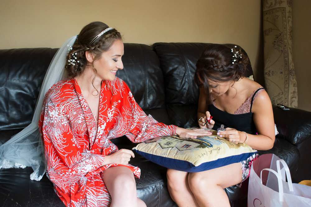Bride having her nails painted before her Bickley Mill Devon wedding