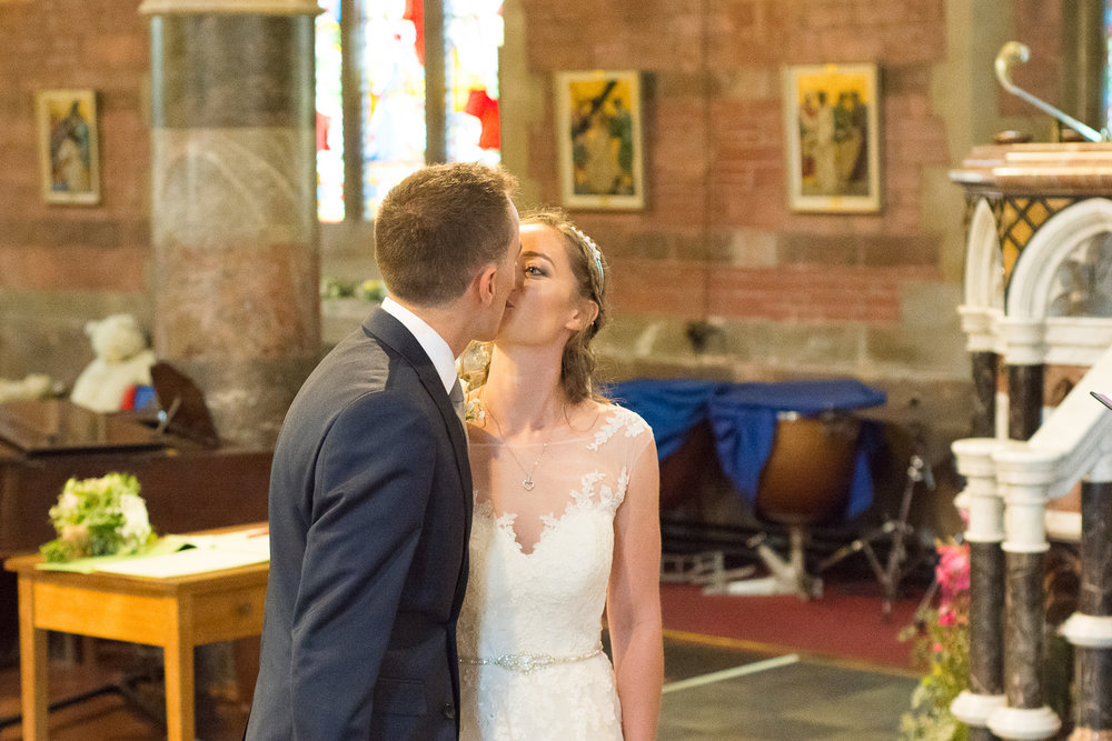 the bride and groom have their first kiss at All Saints Church Babbacombe, Torquay, Devon