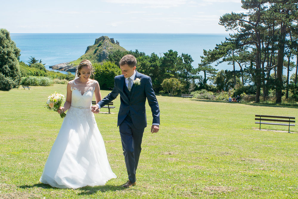 Bride and groom go for a little walk overlooking Thatchers rock in Torquay Devon