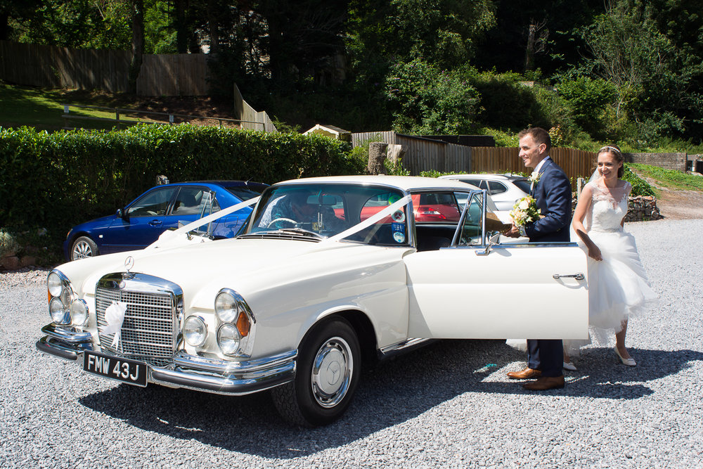 Bride and Groom arriving in style at the Bickley Mill wedding venue in Devon