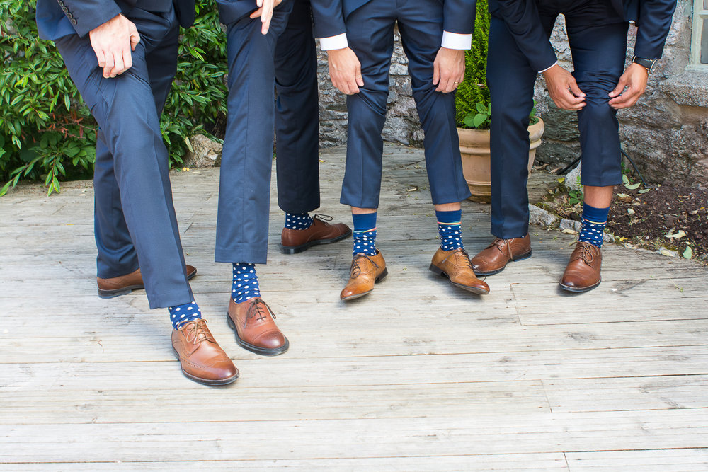 the groomsmen flash their matching sopotty socks on the decking at the Bickley Mill Wedding Venue in Devon