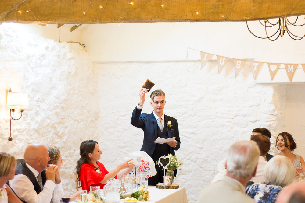 The best man raises a toast (literally) during the speeches at the Bickley Mill in Devon