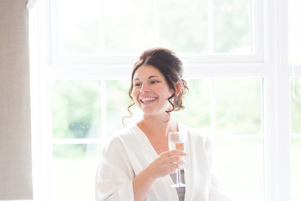 bride stood at the window with a glass in her hand and a huge smile on her face at the lord haldon hotel in devon