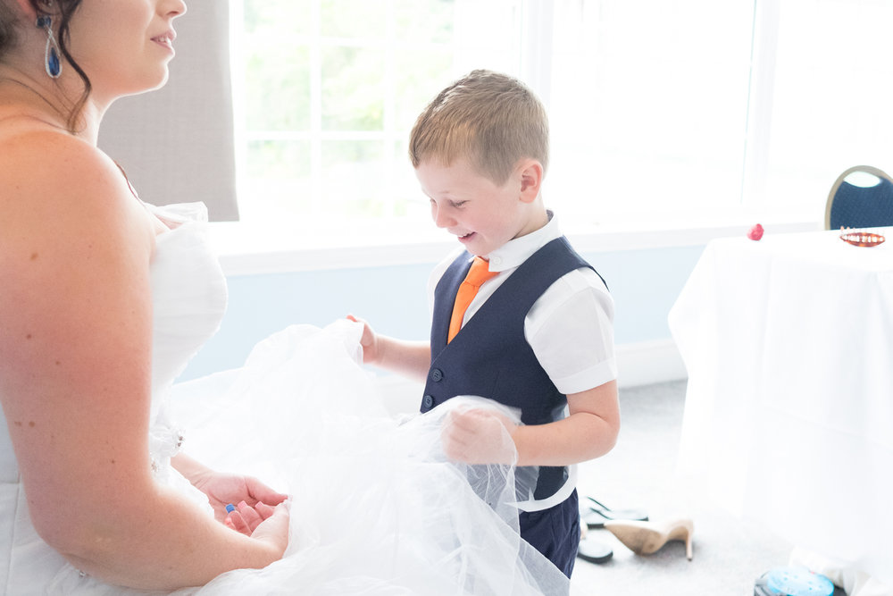 brides little boy looks at and plays with his mums wedding dress
