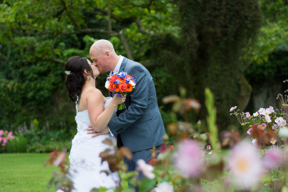 bride and groom kiss by the flowers at The Lord Haldon Hotel in Devon