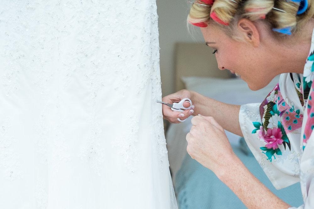 Bride cutting loose threads off her dress in woolacombe devon