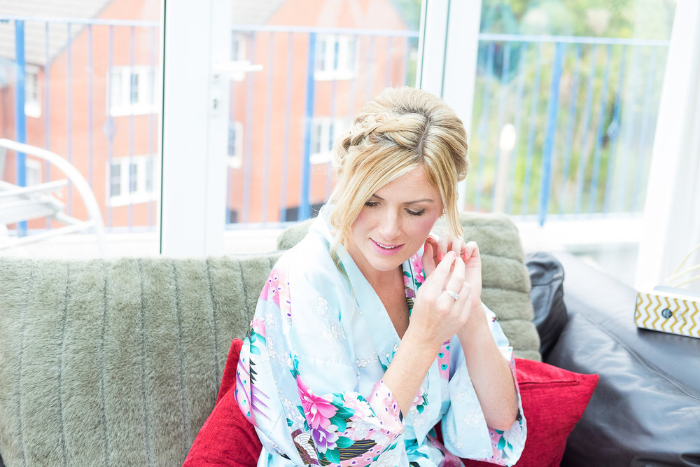 bridesmaid in dressing gown puts her earrings on in woolacombe devon