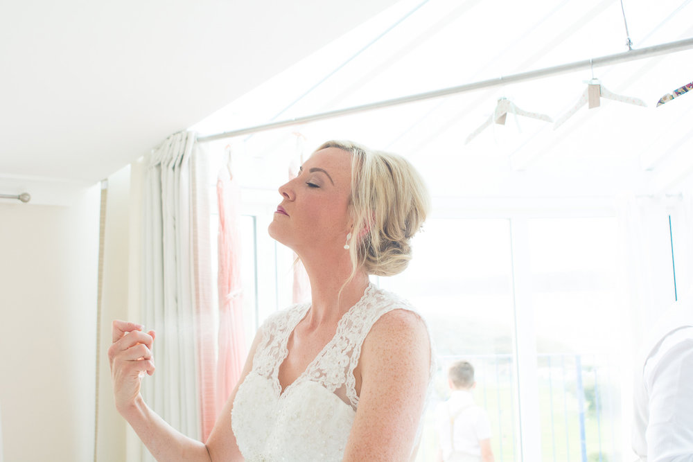 bride putting perfume on in beautiful light in woolacombe
