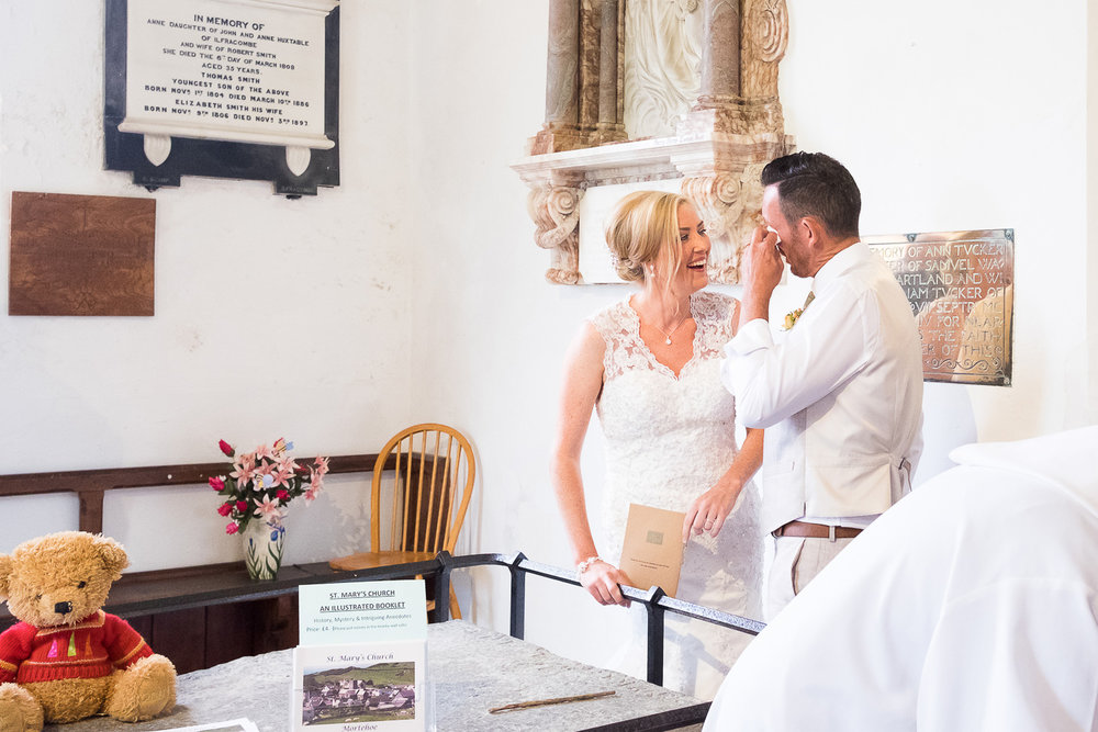 groom wipes happy tears from his eyes at st mary's church in woolacombe