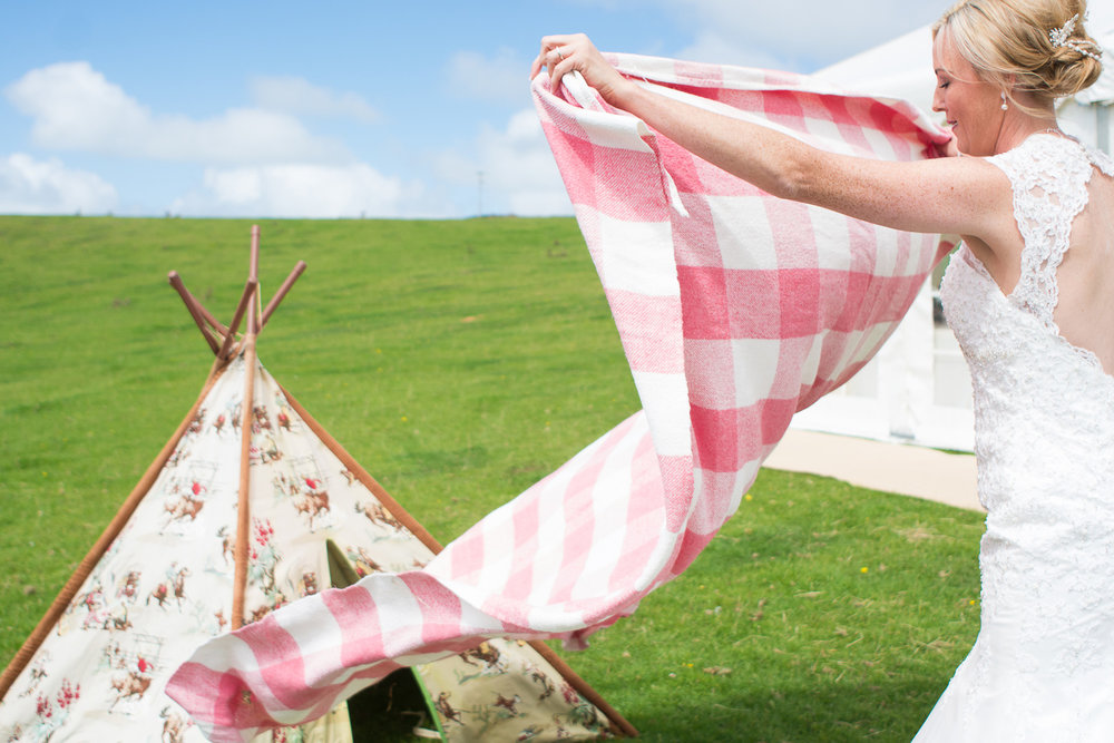 bride lays blanket by the tipi at festival wedding in woolacombe