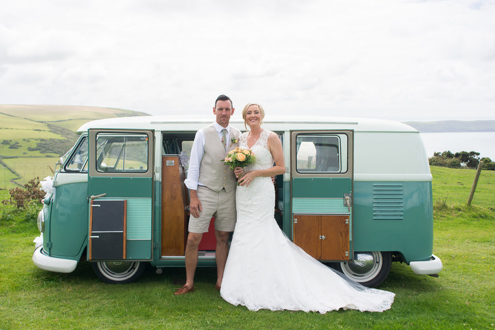 bride and groom with their vw camper on a woolacombe cliff top