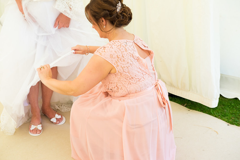 bride puts her flip flops on at festival wedding in woolacombe