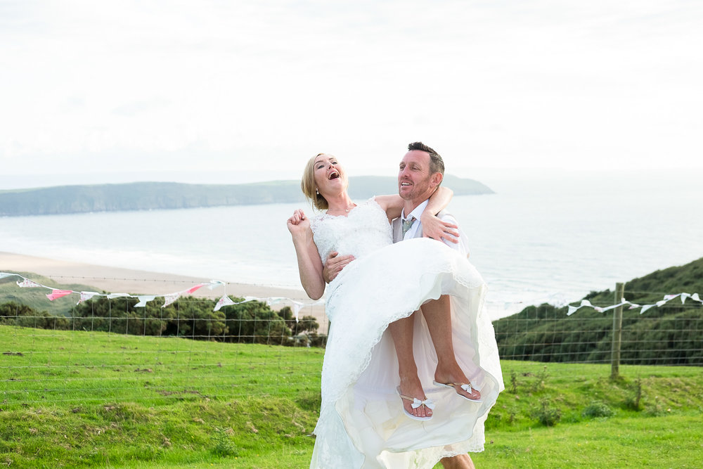 groom lifts up his bride with a beautiful woolacombe seaside view in the background