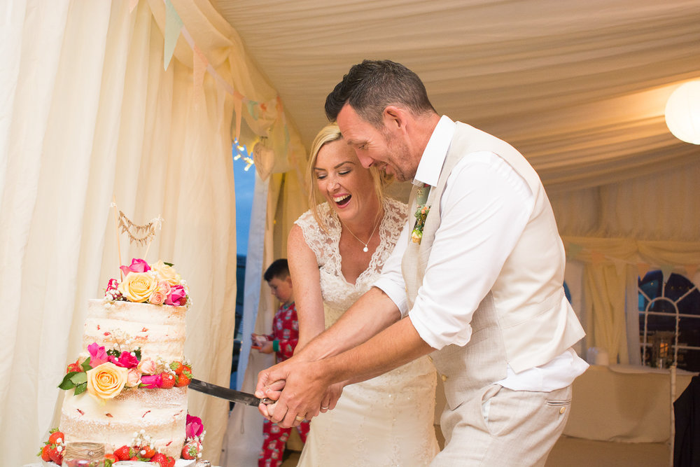 cutting the cake at their woolacombe wedding