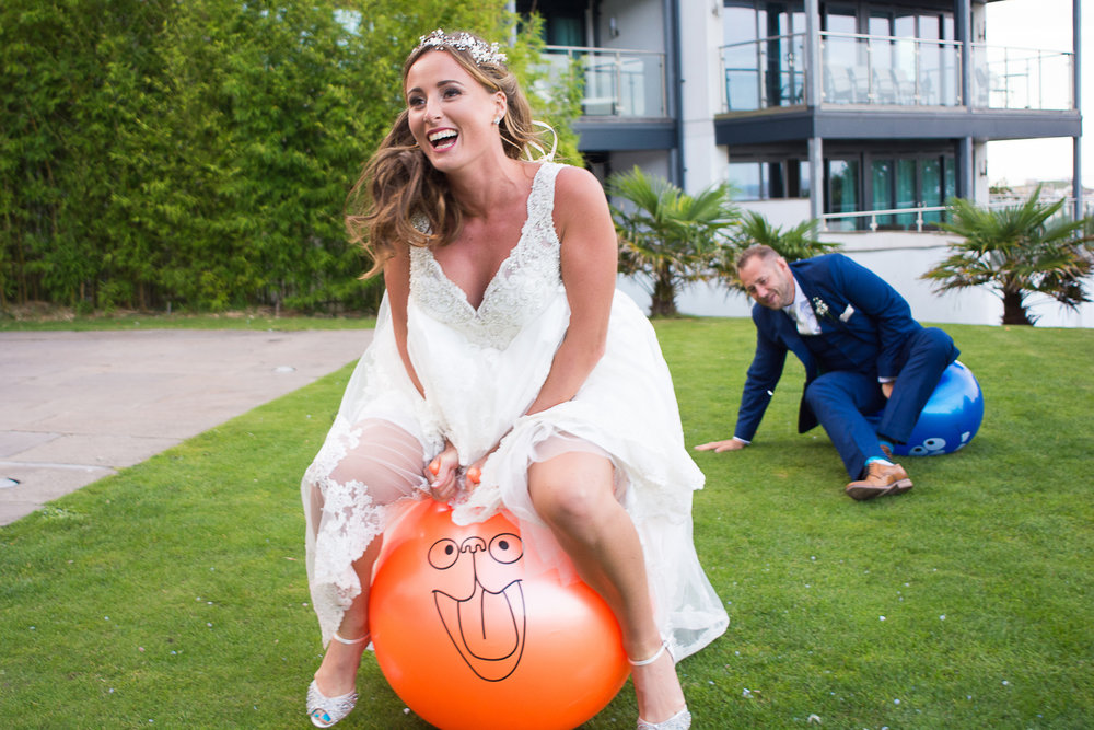 Bride and groom having a space hopper race at the St Ives Harbour Hotel