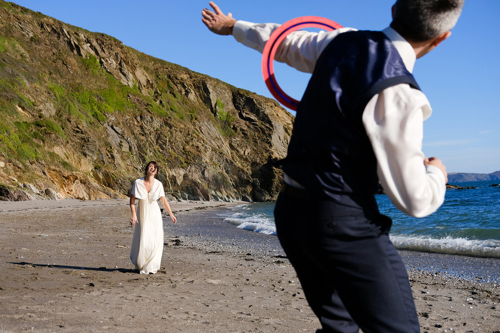 Bride and Groom playing frisbee at Portwrinkle beach in Cornwall