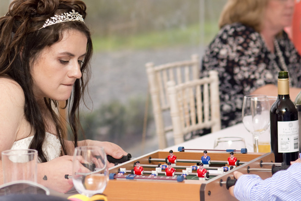 Bride playing table football at her Trevenna Barns wedding in Cornwall