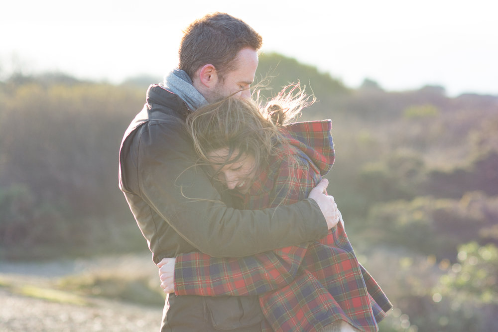 Couple hugging and laughing with wind blowing hair in St Agnes