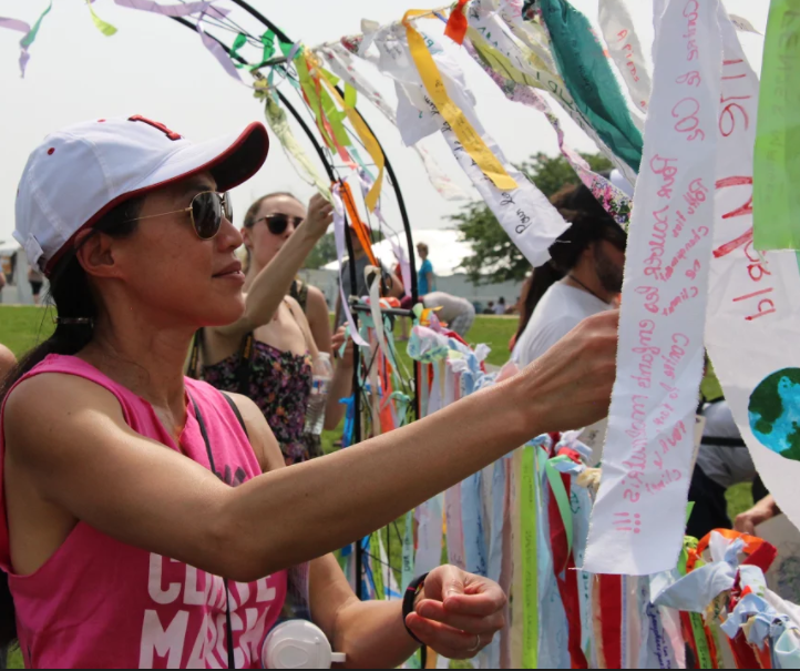 A woman ties her ribbon onto the Climate Ribbon.