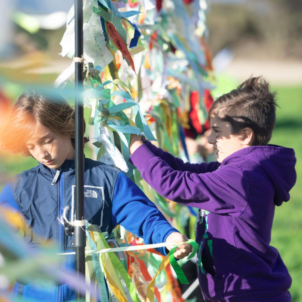 Kids tying ribbons at PCM.9-18.png