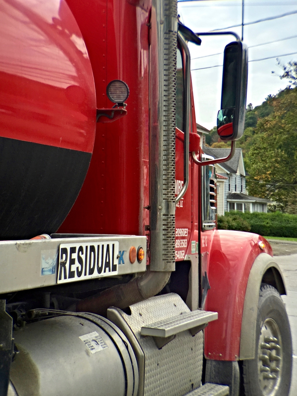 A wastewater truck pulls up beside me at an intersection.
