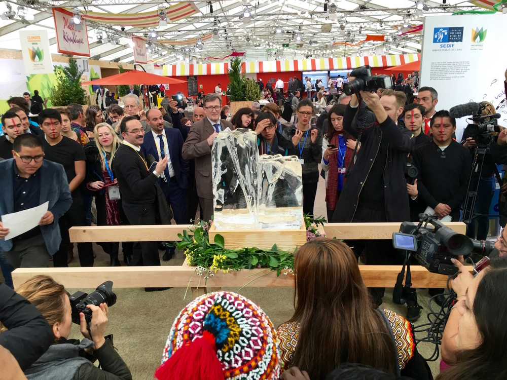 """Inside the """"Green Zone"""", a space for public events adjacent to the Delegate Hall, occasional protests would spring up. This was a mock funeral for Ecuadoreans. Ice and pallbearers."""