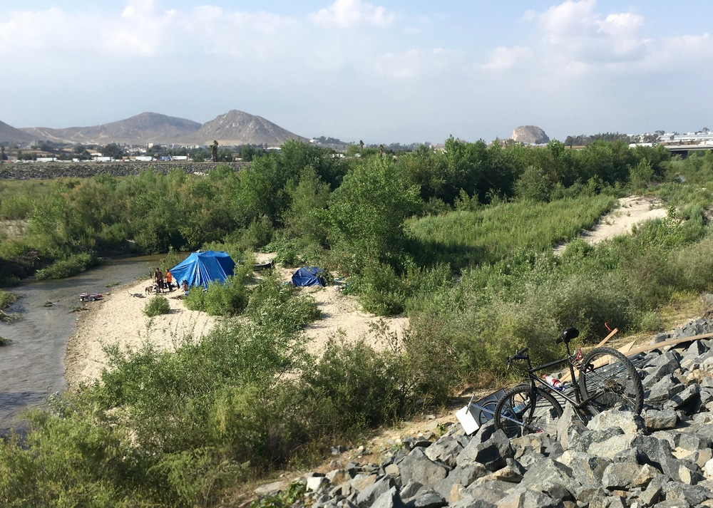 "One of many encampments of ""homeless"" people on the Santa Ana River. I wonder if we would have regarded folks living similarly as homeless 100 years ago?"