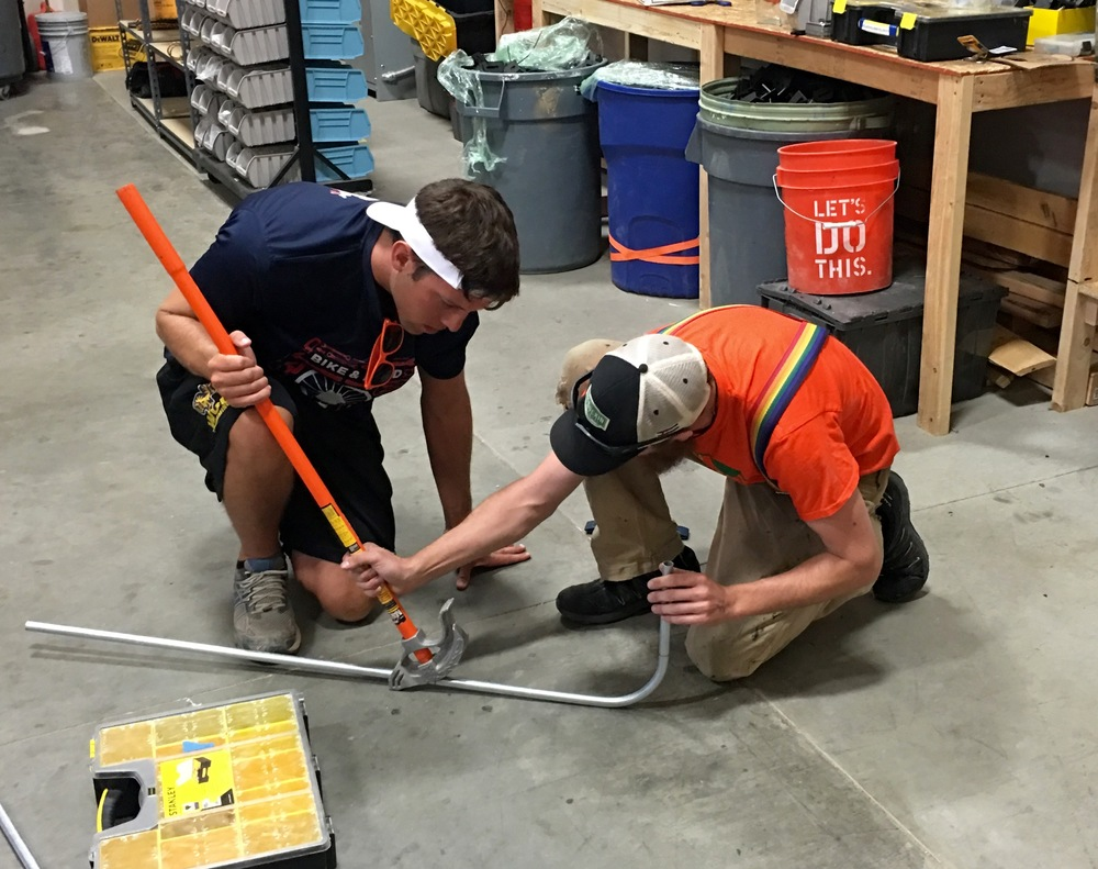 """A workshop in conduit bending for the """"Bike and Build"""" crew at GRID, Colorado."""