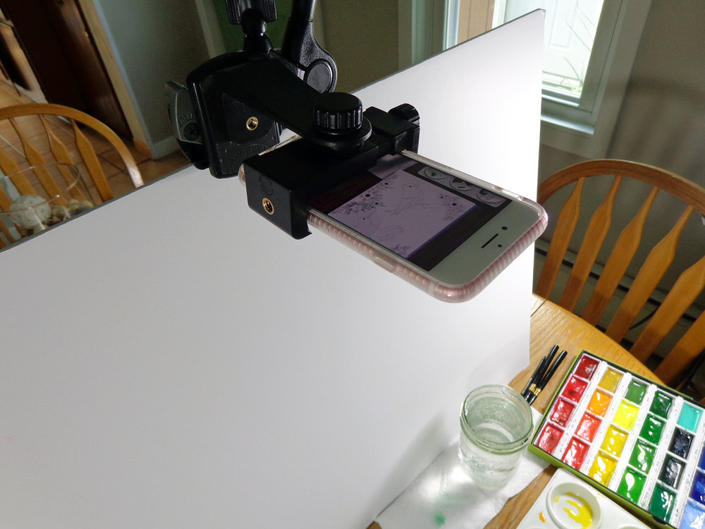The white foam board prevents shadows showing on the paper and bounces light back to my working surface.