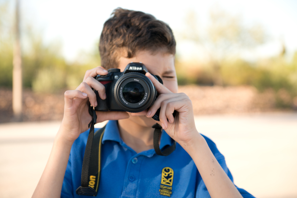 My oldest kid with our oldest nikon, excuse his hair apparently in 5th grade the cool thing to do is let your hair grow as long as possible and leave it wild.