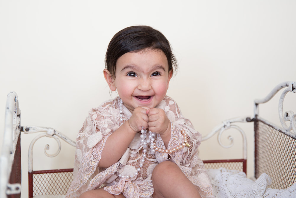 Adorable baby girl in pearls and lace sitting on a vintage bed and smiling. Airdrie baby photographer