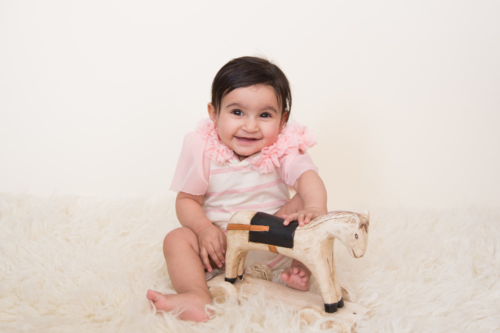 Adorable baby girl with an antique wooden horse smiling and rocking her baby milestone session with Airdrie photographer