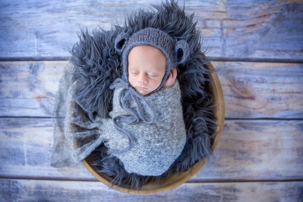 Little newborn baby boy wearing a bear hat in a bowl. Newborn Photographer in Airdrie Alberta