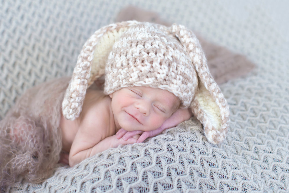 Cute little newborn baby smiling in his sleep and dressed up as a bunny. Great idea for an Easter inspired photoshoot. Captured by Milashka Photography.