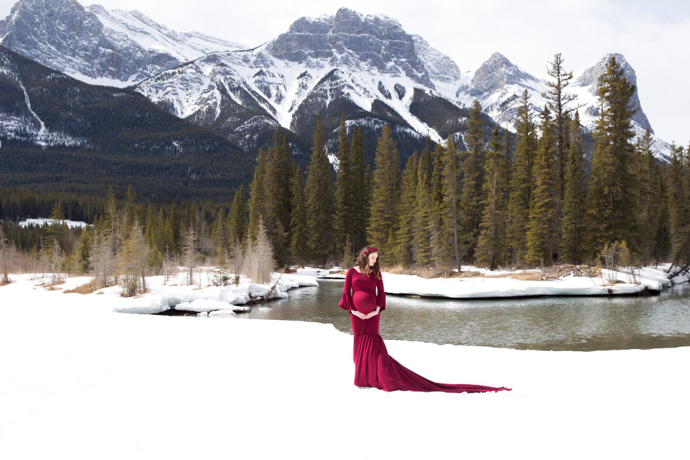 Red Maternity Gown on the White Snow in the mountains. Alberta Maternity Photographer.