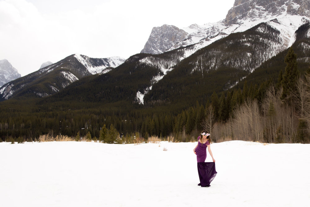 Maternity Photoshoot in the mountains. Mom to be in a purple dress on a snow.