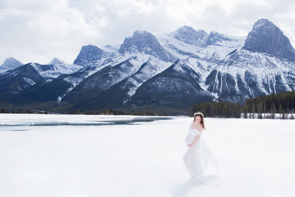 Winter maternity photoshoot in the mountains. Mother-to-be in a white gown. Calgary photographer.