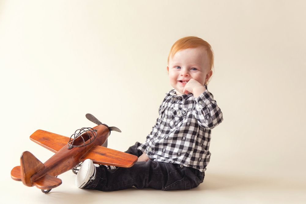 One year old boy with a wooden plane. Airdrie and Calgary child photographer.