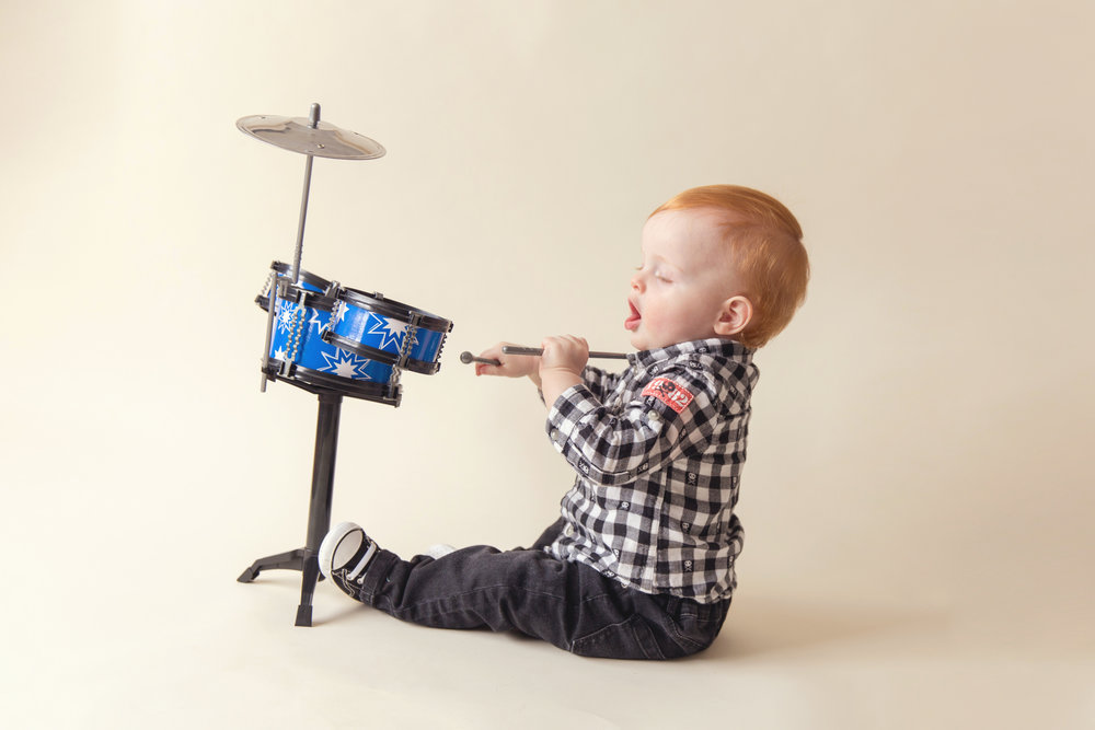 Little redhead boy is playing drums. Calgary and Airdrie Photographer.