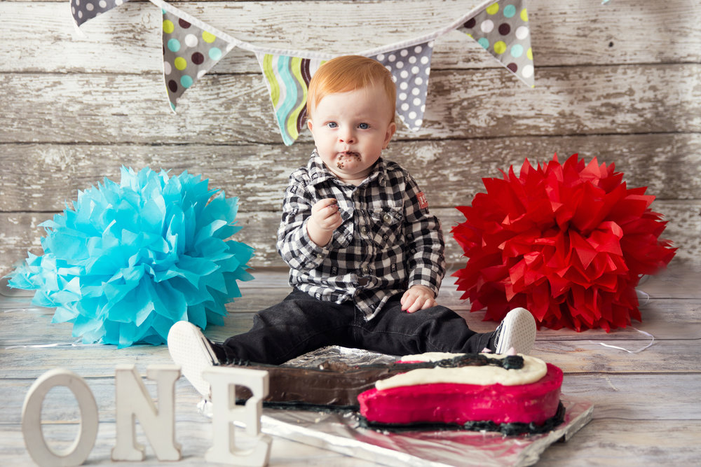 Cakeshmash photoshoot. Little redhead one year old boy is smashing his first guitar cake. Calgary cakesmash photographer.