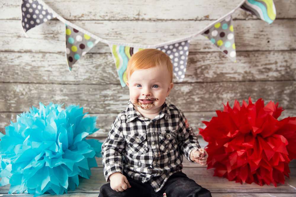 Successful Cakesmash. Little redhead boy is loving his birthday cake. Calgary cakesmash photographer.