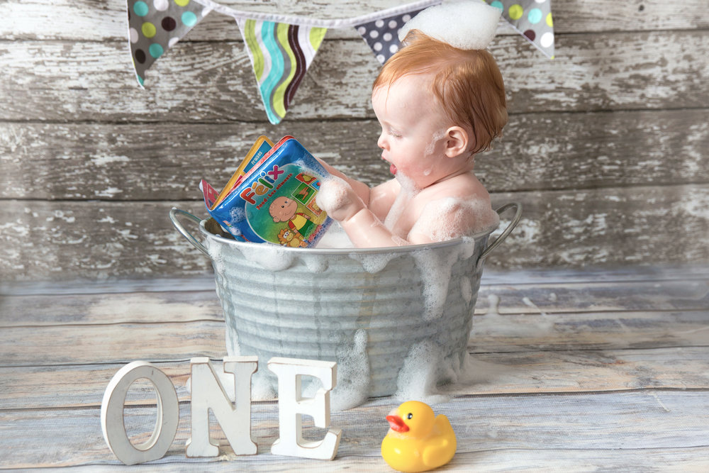 Felix reading a book about Felix. Baby boy enjoying his bubble bath while reading a book after smashing his birthday cake. Airdrie and Calgary Cakesmash photographer.