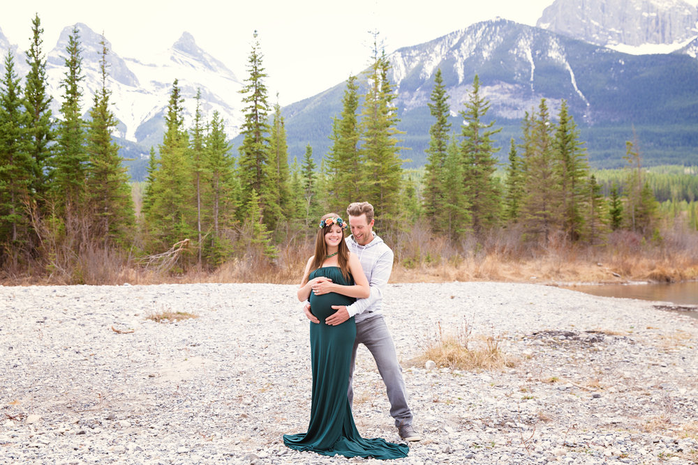Mountain Maternity photoshoot in Canmore, Alberta. Expectant radiant parents-to-be in the mountains. Mom-to-be in a beautiful green gown. Canmore and Calgary Maternity Photographer. Milashka Photography.