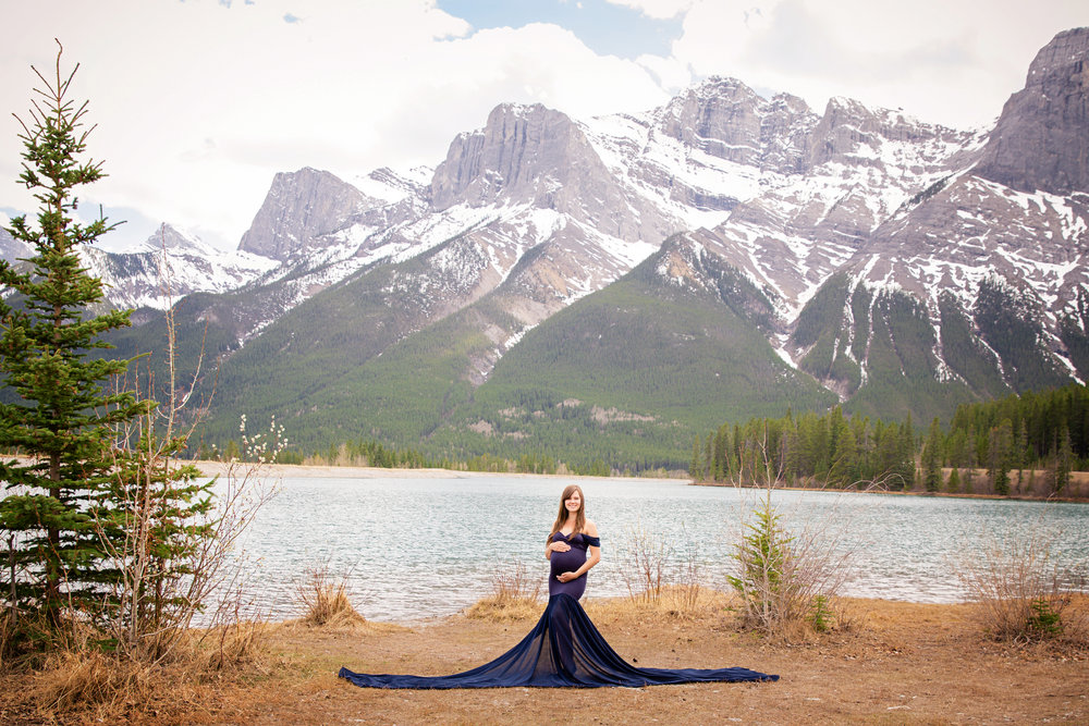 Beautiful mother-to-be in a blue gown in the mountains. Canmore, Alberta. Canmore maternity photographer. Milashka Photography